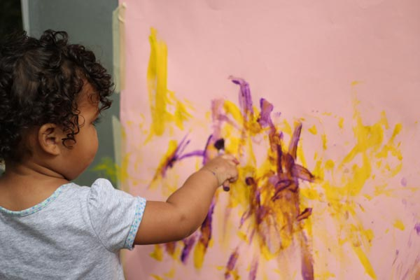 toddler finger painting at the asi children's center