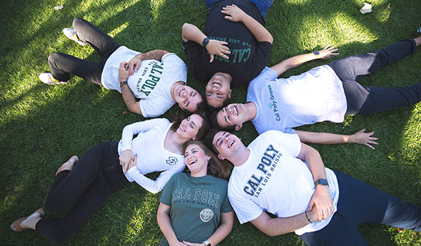 an aerial photo of students smiling on the grass wearing cal poly t-shirts