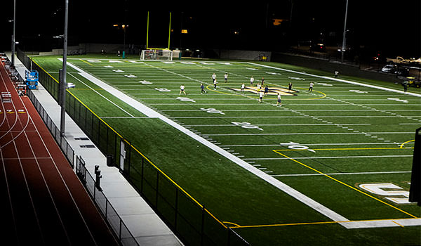 asi doerr family field with students playing at night