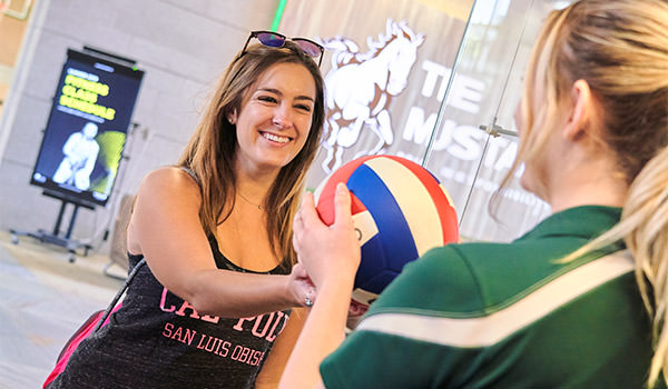 student checking out a volleyball from the cal poly recreation center pro shop