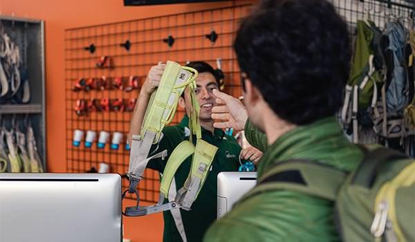 asi staff handing a climbing harness at the cal poly recreation center climbing park