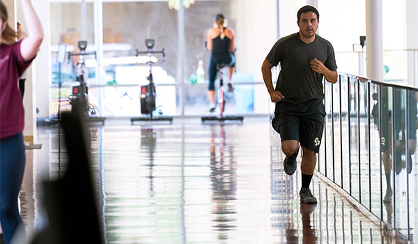 student running at the cal poly recreation center indoor track