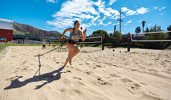 student running in the sand at the cal poly recreation center outdoor facilities