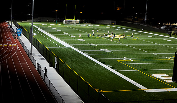 students playing on the doerr family field at night