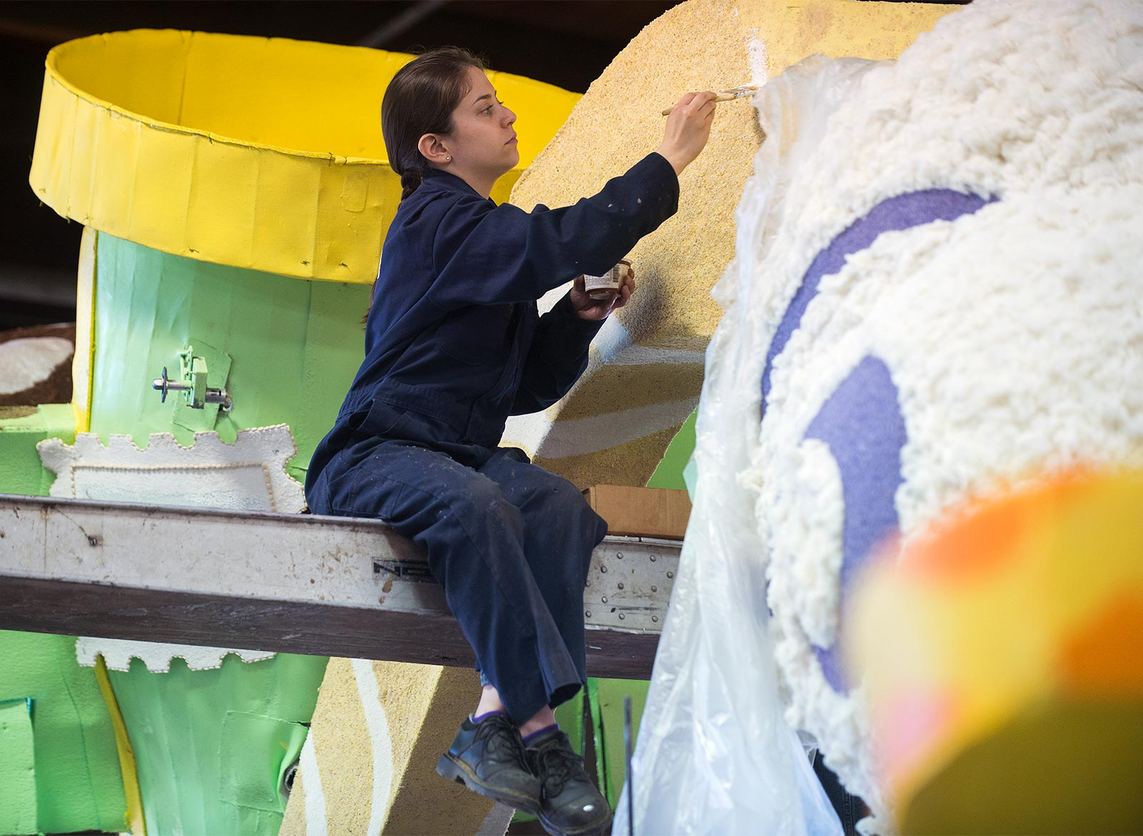 student painting the cal poly rose float