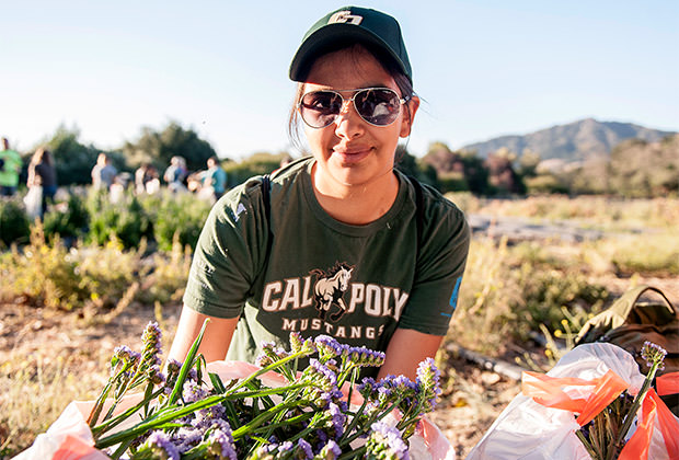 photo of a cal poly student with flowers for the cal poly rose float