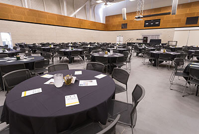 Empty table rounds set up for an event at the ASI Cal Poly Recreation Center MAC