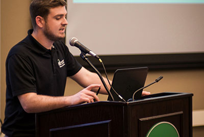 An ASI Cal Poly student government representative speaking into a microphone at a podium