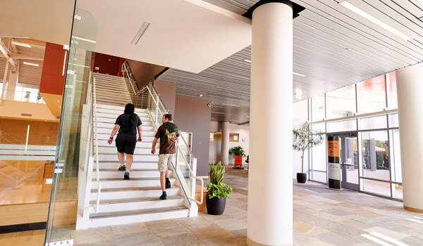 Two Cal Poly ASI Recreation Center members walking up the stairs