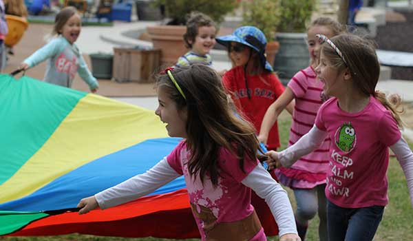 Children at the ASI Cal Poly Children's Center playing with a rainbow parachute